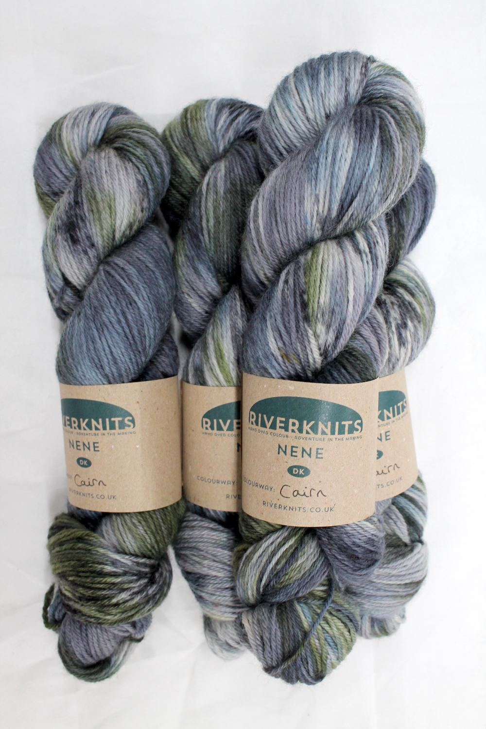 A pile of skeins of Nene DK in variegated greys, slate blue-grey, and moss green