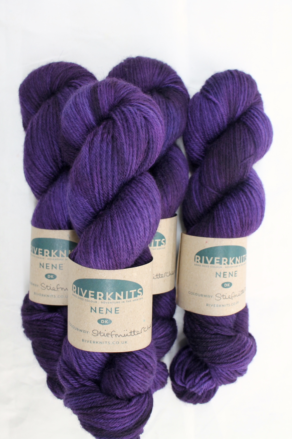 A pile of skeins of Nene DK in deep purple
