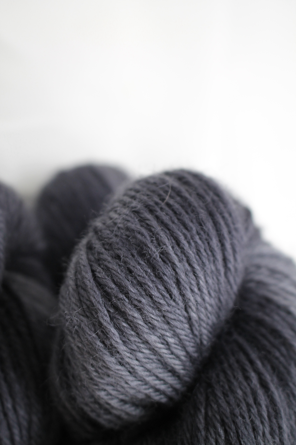 A pile of skeins of Nene DK in charcoal grey