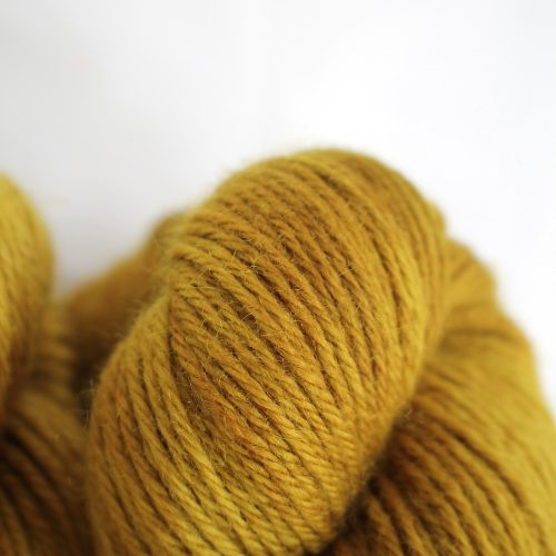 A pile of skeins of Nene DK in golden mustard
