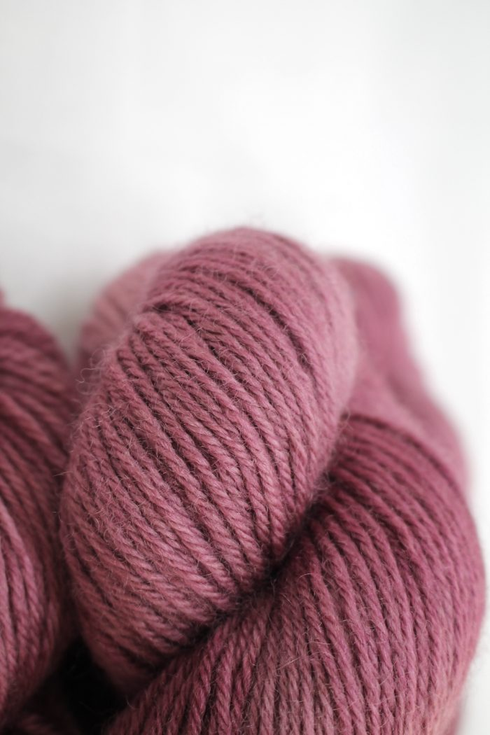 A pile of skeins of Nene DK in faded rose pink