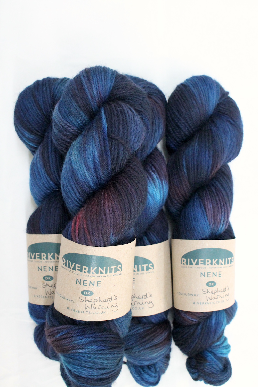 A pile of skeins of Nene DK in variegated deep blues, teals, and burgundy red