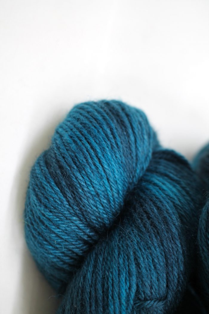 A pile of skeins of Nene DK in deep turquoise teal