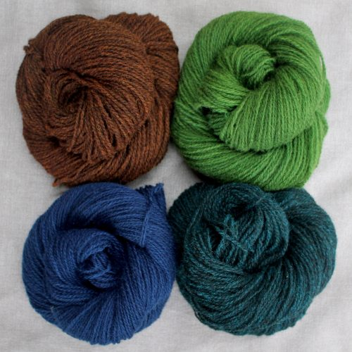 A group of 4 skeins in rich brown, navy blue, teal, and green