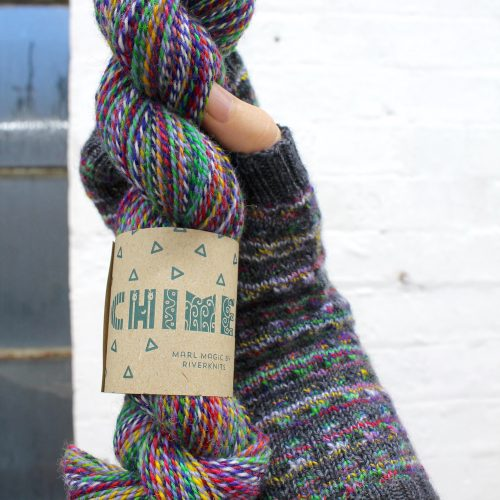 A mittened hand holding a skein of Chimera in the same colours as the mitten