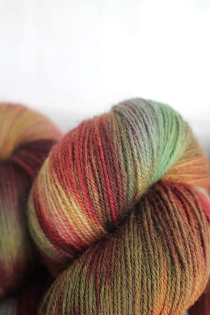 Skeins dyed in variegated wine red, browns, and blue-green