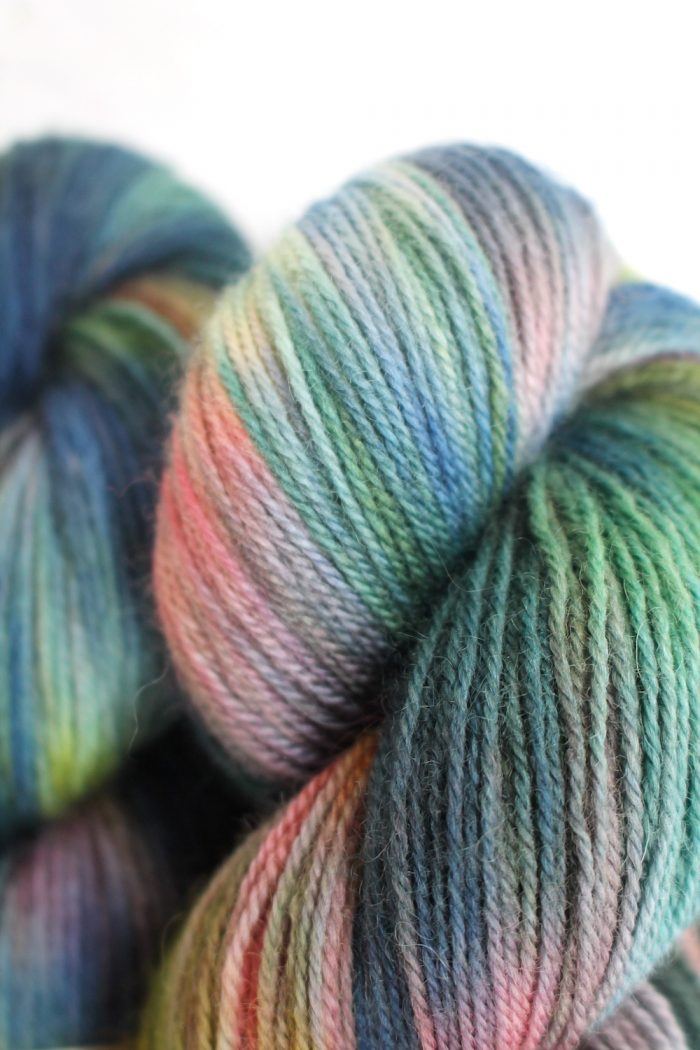 Skeins dyed in variegated soft blues, greens, and pink