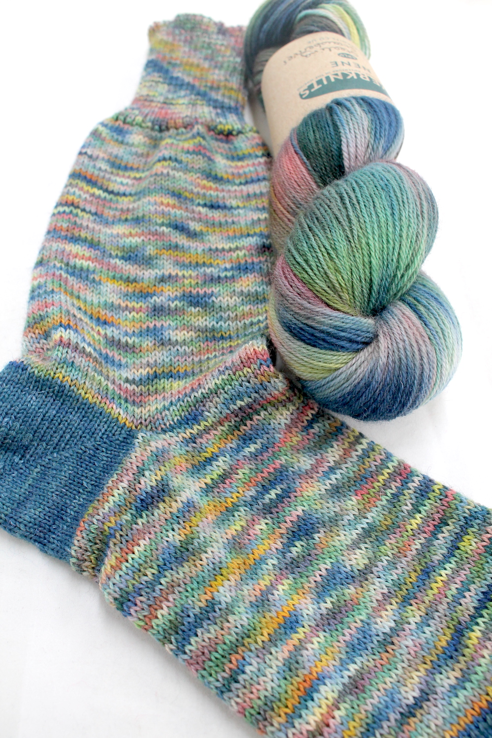 A sock knitted in the Stealing Strawberries colourway
