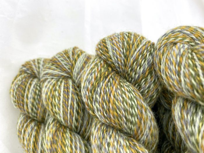 Close up of marled yarn in mint and khaki green, mustard, and mid greys.