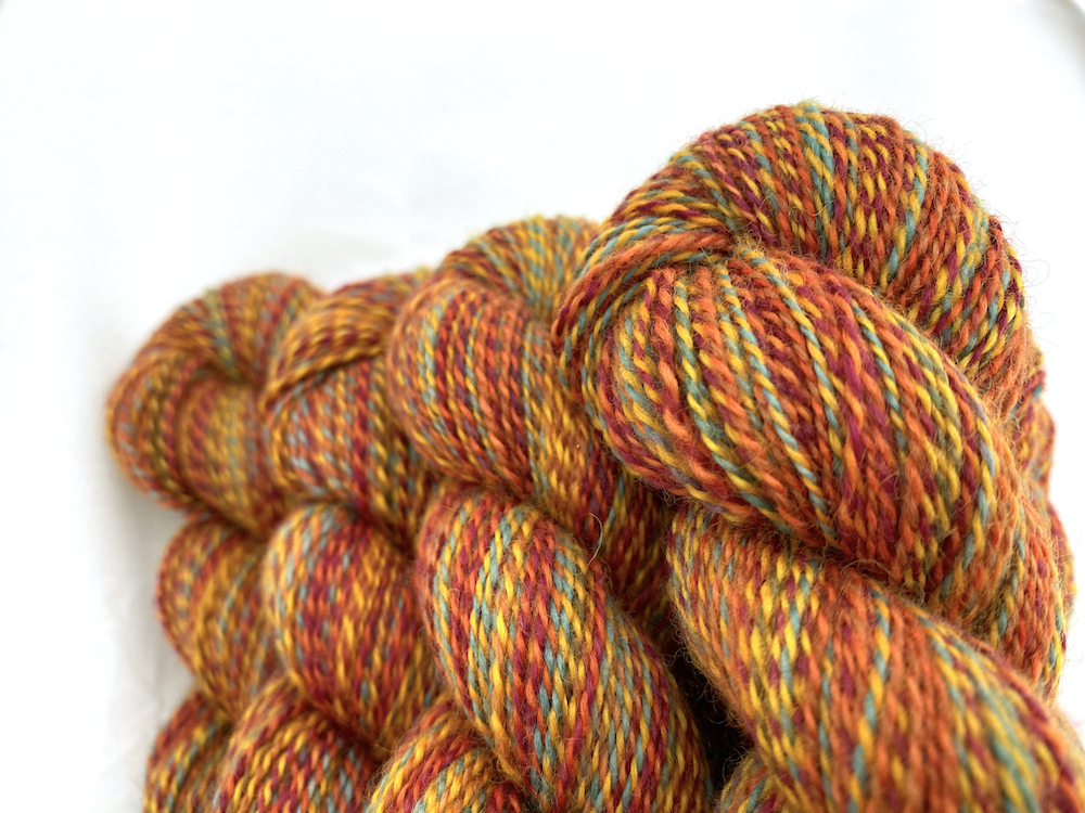 Close up of some marled yarn in reds, oranges, golds, and a tiny bit of sage green.