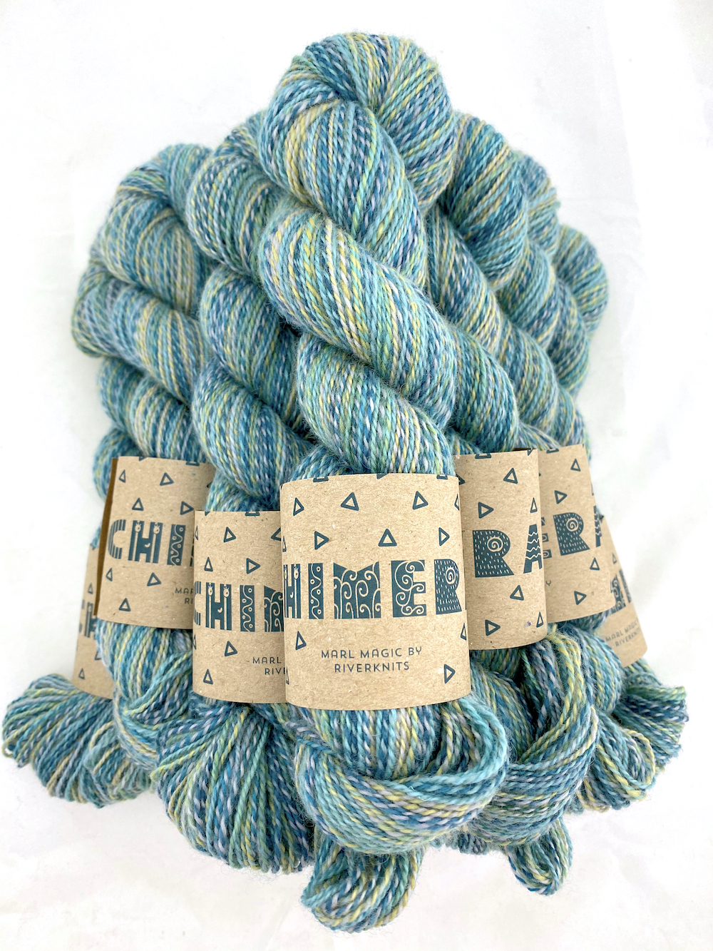 A pile of marled yarn in soft teal, blue, and a tiny bit of sandy yellow.