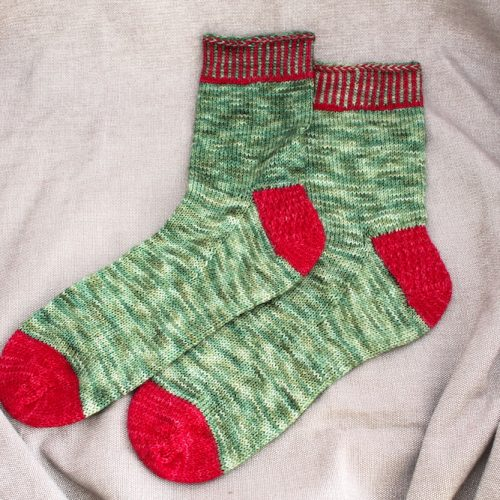 A pair of Festive Feet socks in green with red heels, toes, and cuff detail