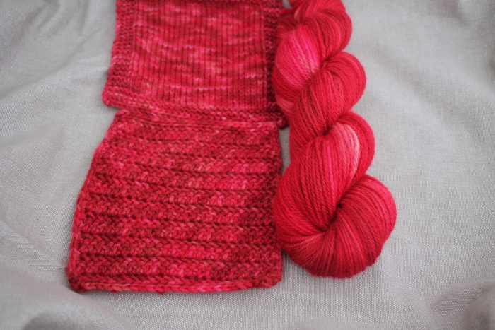 A skein and two swatches of Lyn DK in the Rosehip colourway