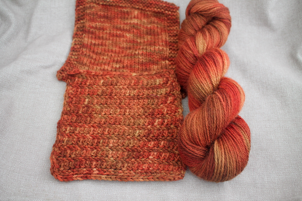 A skein and two swatches of Lyn DK in the Roast Chestnut colourway