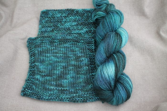 A skein and two swatches of Lyn DK in the Gathering colourway