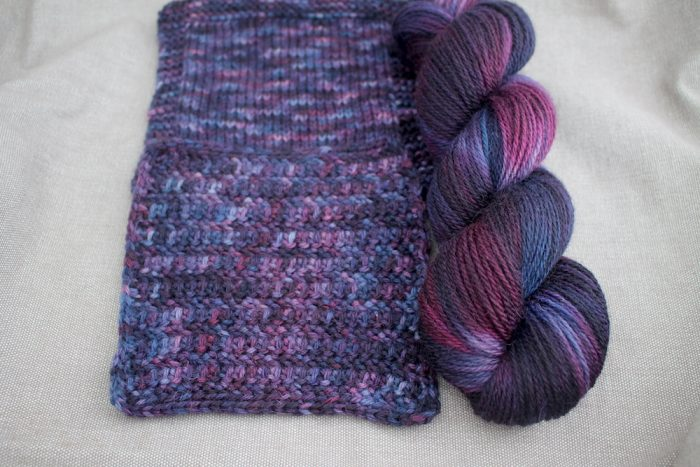 A skein and two swatches of Lyn DK in the Sloe Gin colourway