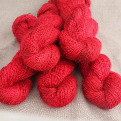 A pile of skeins of Aysgarth in the Rosehip colourway