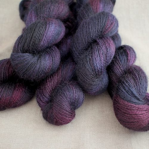 A pile of skeins of Aysgarth in the Sloe Gin colourway