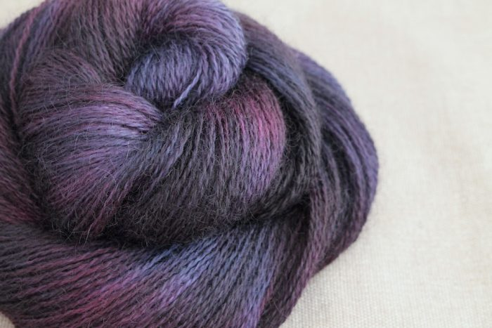 A skein of Aysgarth 4 Ply in the Sloe Gin colourway