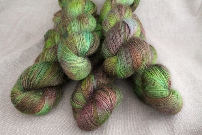 A pile of skeins of Aysgarth in the Bramble colourway