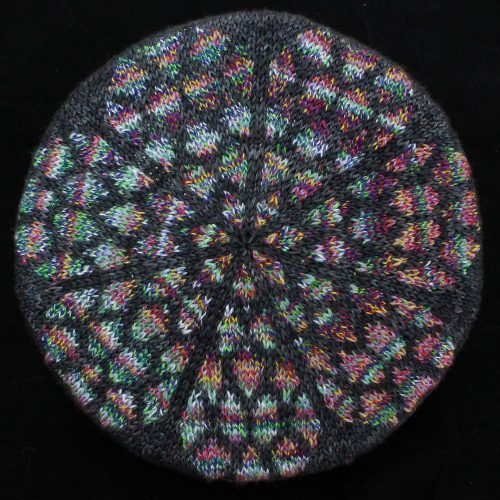 The crown of the Rose Window tam in Christmassy stained glass colours