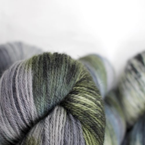 A pile of skeins of Nene 4 Ply in variegated greys, slate blue-grey, and moss green