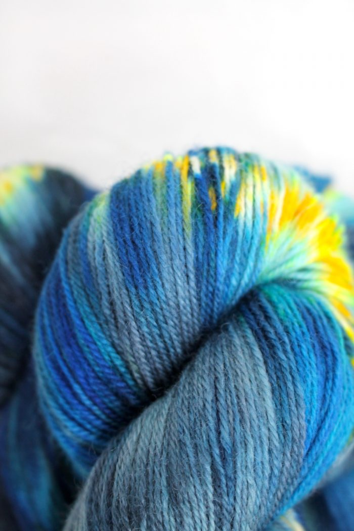 Skeins of yarn that are variegated from dark to light blue with bright yellow speckles