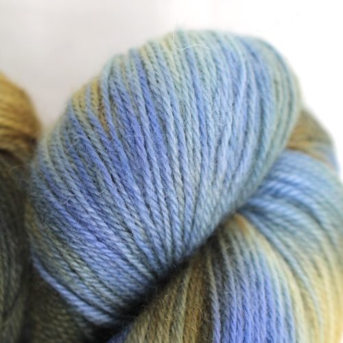 A pile of skeins in sky blue, white, and sandy brown