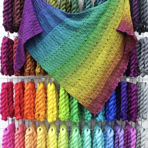 A rainbow shawl hanging on a wall of rainbow mini skeins