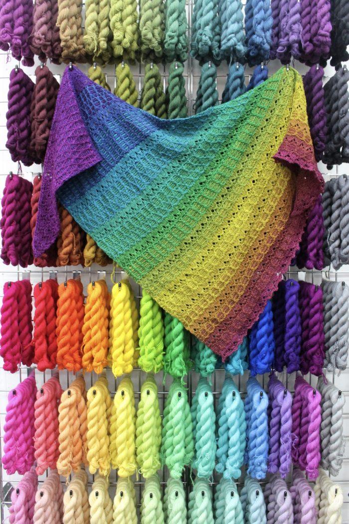 A rainbow shawl hanging on a wall of rainbow mini skeins