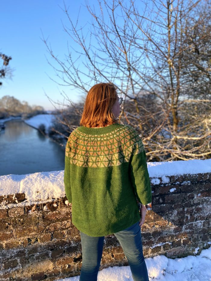 Becci wearing a green Prism jumper in the snow