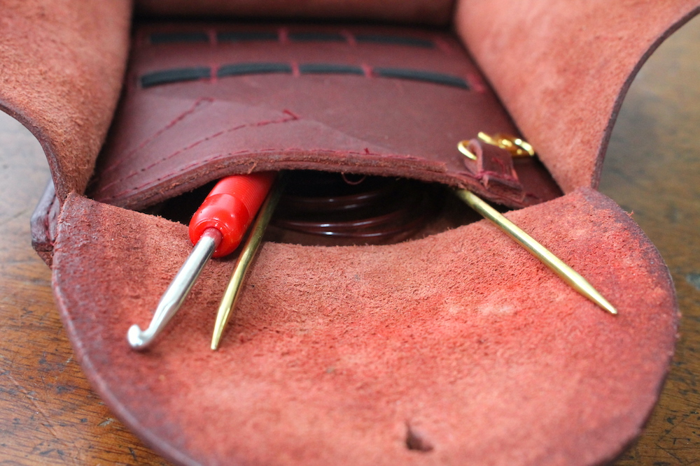 Open pocket on crafter's wallet showing a crochet hook and circular needle inside