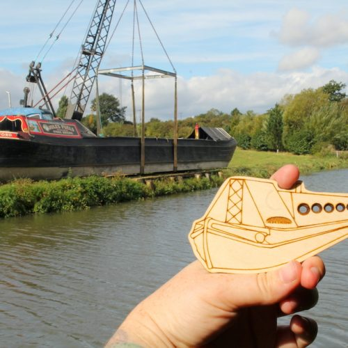 Narrowboat needle gauge in foreground with a traditional working boat in the background